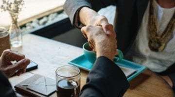 two people sitting at a desk, shaking hands, ensuring that their website is secure